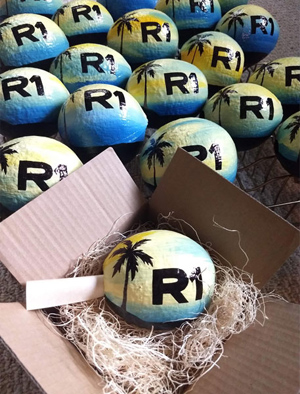 Painted hollow coconuts with scrolled invitation make green and eco-friendly gifts